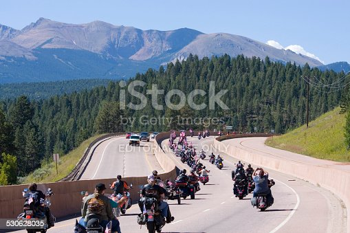 Woodland Park, Colorado, USA - August 16, 2014: Motorcycle riders, many with American flags ride west from Woodland Park on Highway 24 past Pikes Peak in a rally to honor U.S. veterans. The ride runs from Woodland Park, Colorado to Cripple Creek, Colorado.