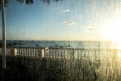Salvador, Bahia, Brazil - June 17, 2021; Porto da Barra beach balustrade seen through the dirty glass of the bus stop.