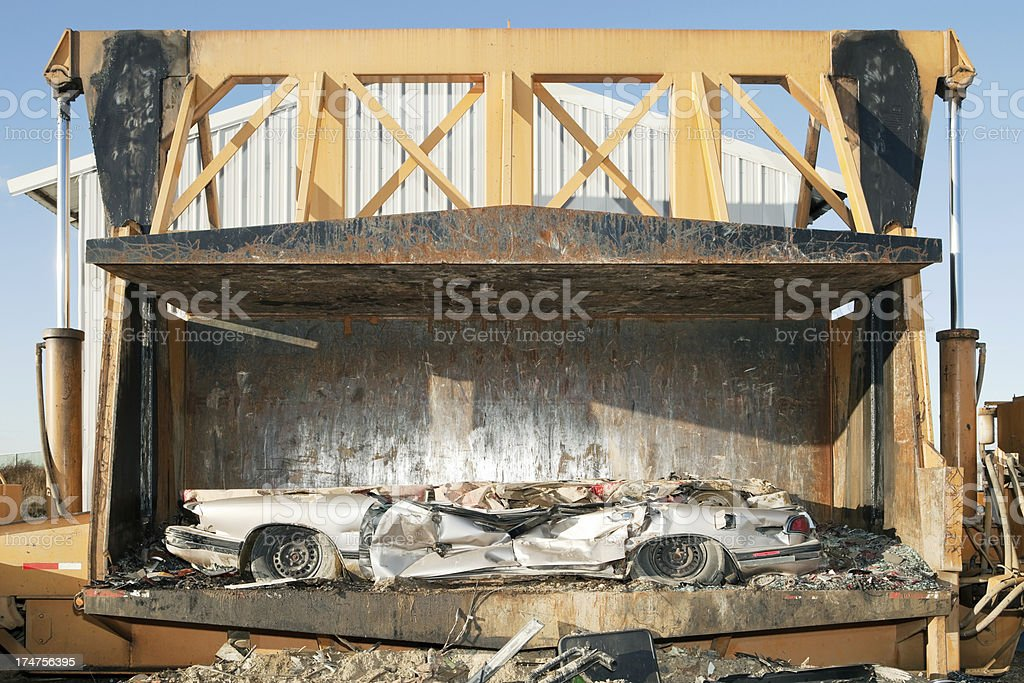 Salvage Yard Car Crusher with Smashed Vehicles stock photo