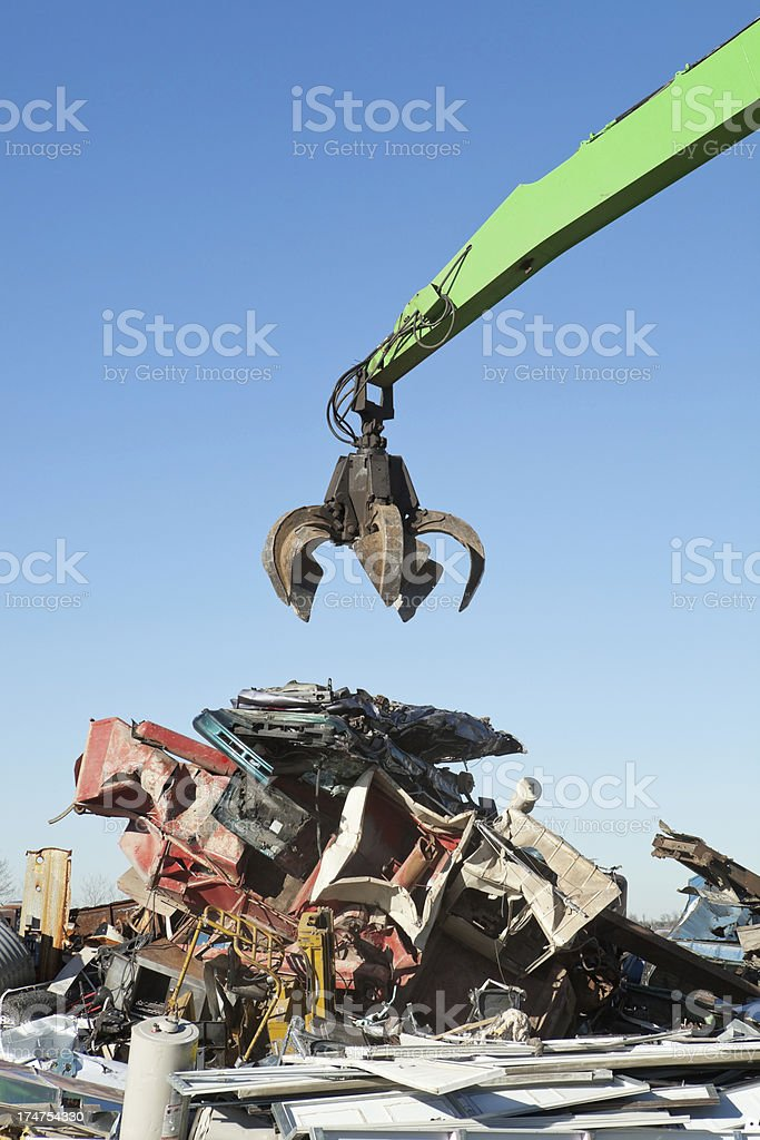 Salvage Yard Grappling Claw Above Crushed Cars and Scrap Pile stock photo