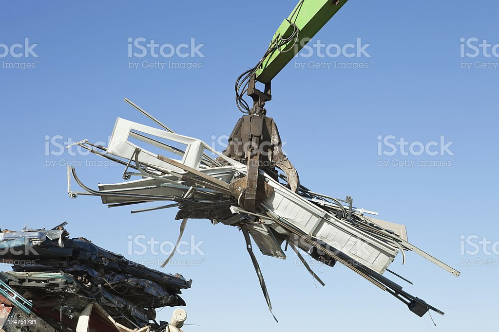 Salvage Yard Grappling Claw Gripping Scrap Metal royalty-free stock photo