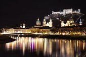 View of the old city of Salzburg, Austria, from the river Salzach by night