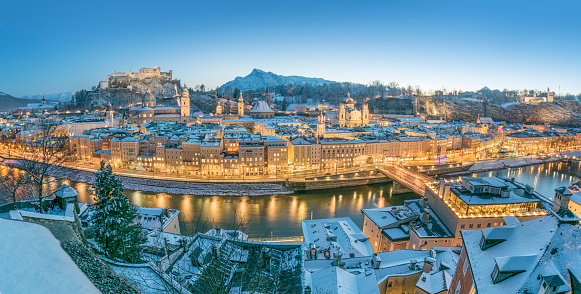 Beautiful detailed Panorama of Salzburg with the famous Hohensalzburg Festung covered in fresh Snow at sunset with the street lights just gone on. The most famous town in Austria where Mozart was born.