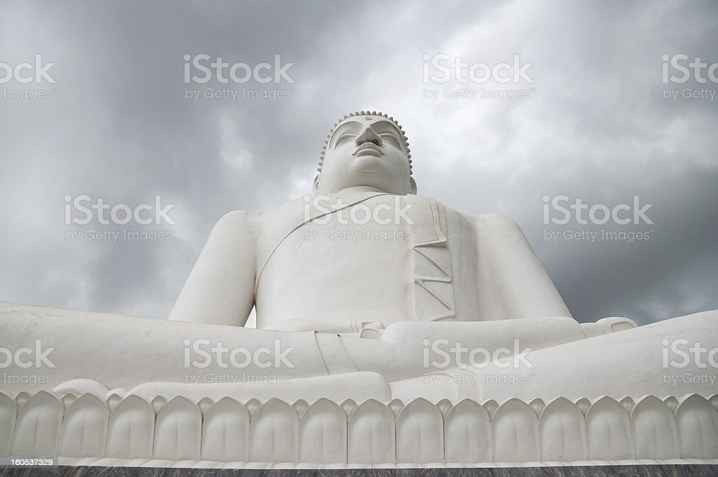 Samadhi Buddha statue with storm clouds and ray of sunlight royalty-free stock photo