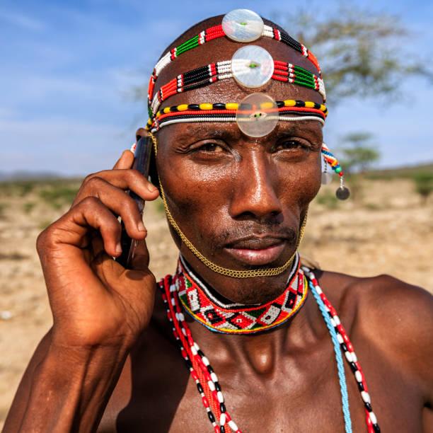 Samburu tribe warrior using mobile phone, central Kenya, East Africa stock photo