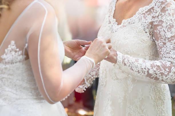 hetzelfde geslacht homo lesbische bruid oplegt ring vinger tijdens de huwelijksceremonie - lesbische stockfoto's en -beelden