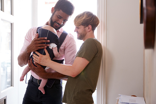 istock Same Sex Male Couple With Baby Daughter In Sling Opening Front Door Of Home 1177241675
