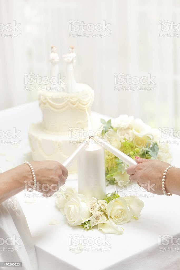 Same Sex Marriage Brides Lighting Candle With Wedding Cake Stock