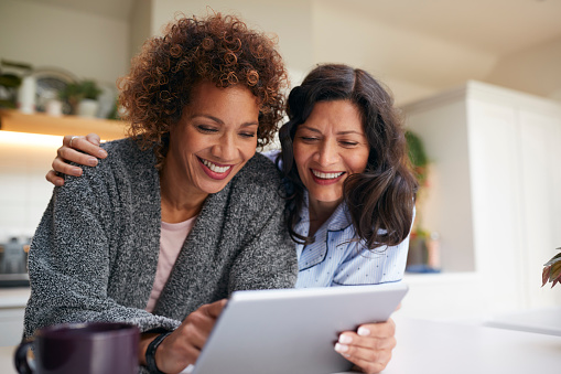 Same Sex Mature Female Couple At Home In Kitchen In Pyjamas Drinking Coffee With Digital Tablet