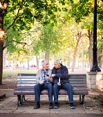 Happy Asian Senior couple laughing while sitting on the bench in the park