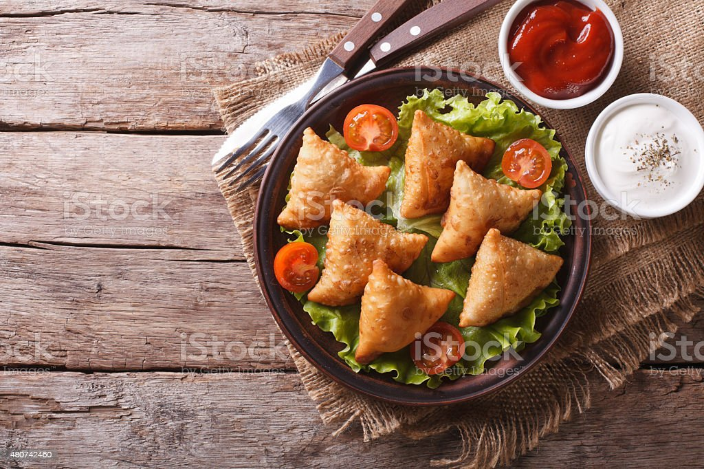 samosa on a plate with sauce, horizontal top view stock photo