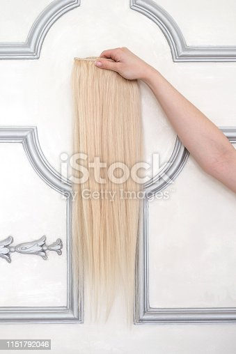 Blond hair extension in female hand