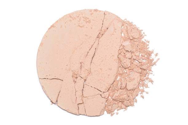 A sample of face powder in white. Beige round cracked powder palette stock photo