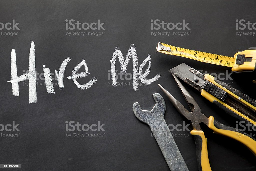 sample of work tools and 'hire me' written on blackboard. stock photo