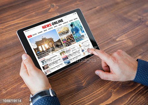 Sample online news website on tablet, unrecognizable male using tablet, top view.