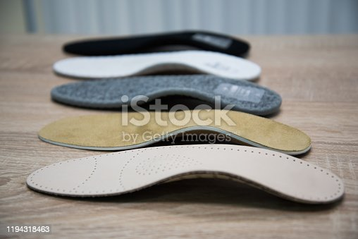 Orthopedic insoles are lined up on a wooden surface. samples of different orthopedic insoles. insoles with a variety of coating.