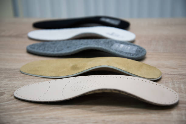 samples of different orthopedic insoles. insole with a variety of coating Orthopedic insoles are lined up on a wooden surface. samples of different orthopedic insoles. insoles with a variety of coating. inserting stock pictures, royalty-free photos & images