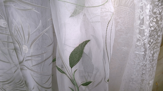 Samples of different types of white luxury tulle. Embroidery of green leaves. Delicate fabric background. Textiles and Apparel industry development. Craft. Idea for home decor and interior.