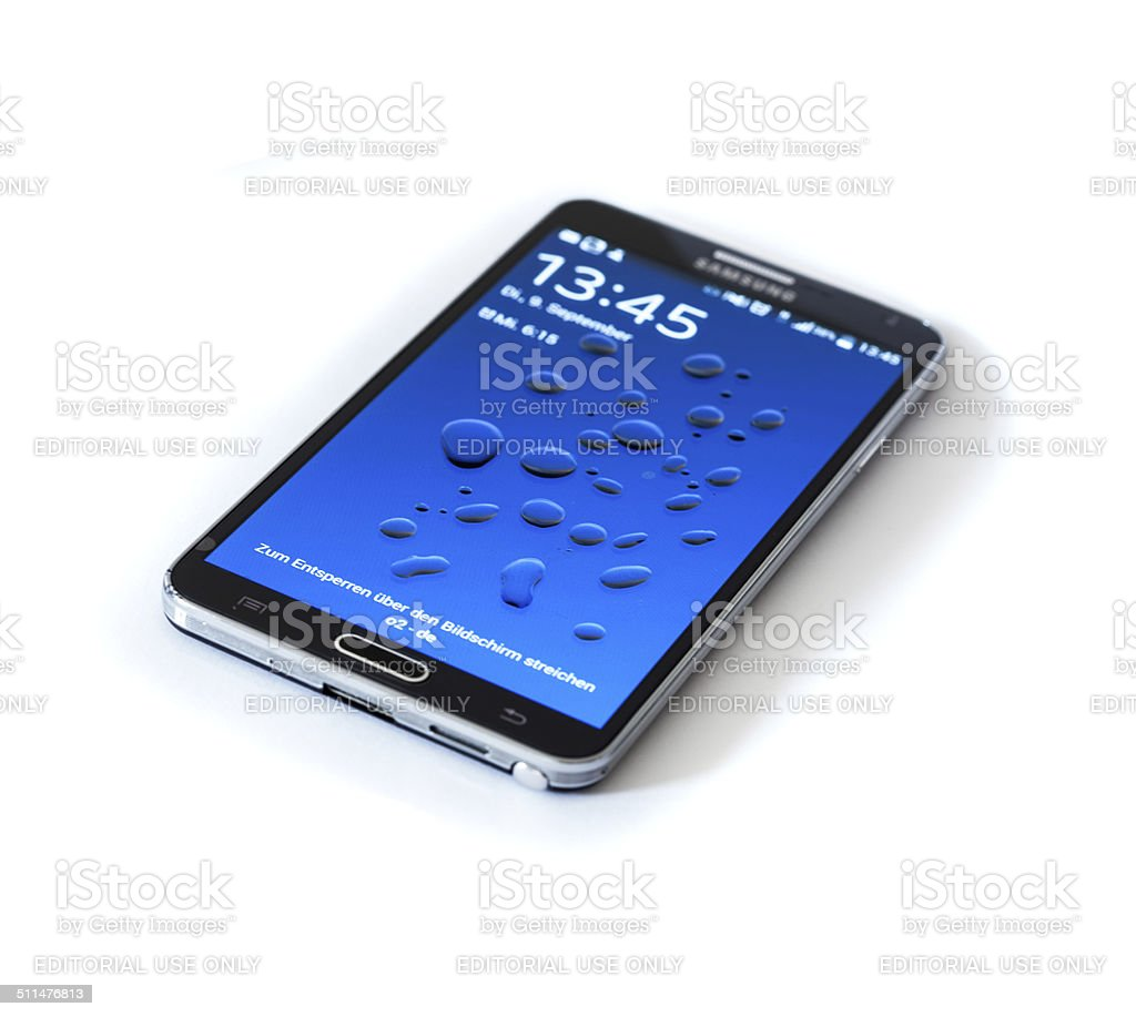 Samsung Galaxy Note 3 with water drops on display, isolated stock photo