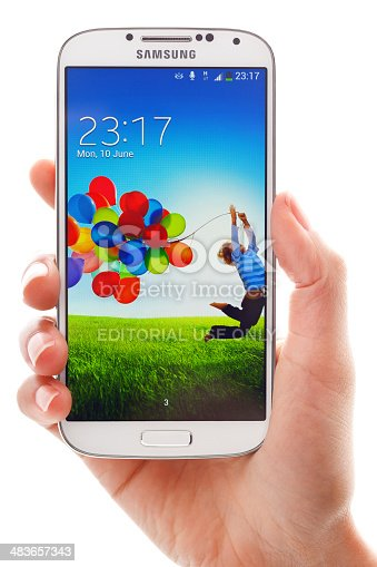London, UK - June 11, 2013: Studio shot of woman's hand holding Samsung Galaxy S4 smartphone. The telephone is supported with 5