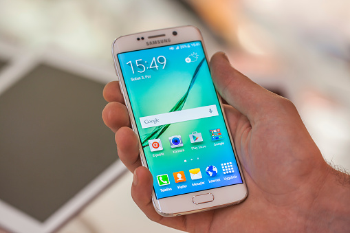 New York, USA - July 26, 2015: White Pearl colored Samsung Galaxy S6 Edge smartphone in hand in a tecknomarket.Samsung Galaxy S6 is supported with 5.1