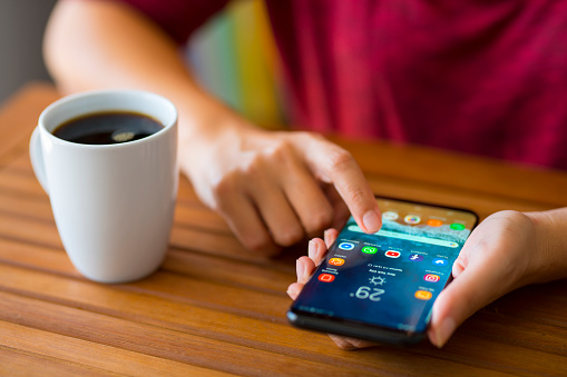 Antalya, Turkey - July 3, 2018: Hand holding a smart phone on a wooden desk. The smart phone is an Samsung Galaxy S9 plus. Samsung Galaxy is a touchscreen smart phone produced by Samsung Electronics.