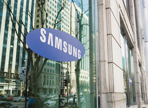 Seoul, Republic of Korea - March 26, 2013: The Samsung logo on the window of one of the South Korean company's offices in Gangnam, central Seoul, with cars and people on the street reflected  in the window.