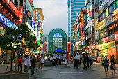 Samsung Plaza (AK Plaza Bundang Store) and pedestrian street with colorful advertisements of stores and restaurants at sunset, Seoul, South Korea. Incidental people walking around and blue sky with clouds are in the image.
