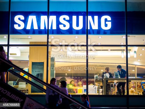 Bangkok, Thailand - November 1, 2012: Exterior view of a Samsung shop in the Siam Square area of Bangkok at night. people can be seen inside the store and making their way up an escalator outside. Image captured from the public walkway.