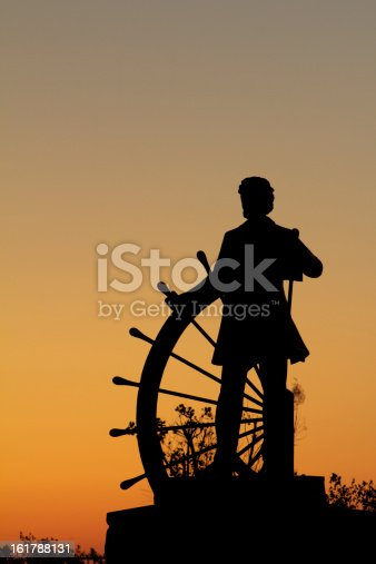 Sunrise silhouette of author Samuel Clemens.   The statue, of Clemens taking the helm of the paddleboat steering. Overlooks the Mississippi River, in Hannibal, Missouri.