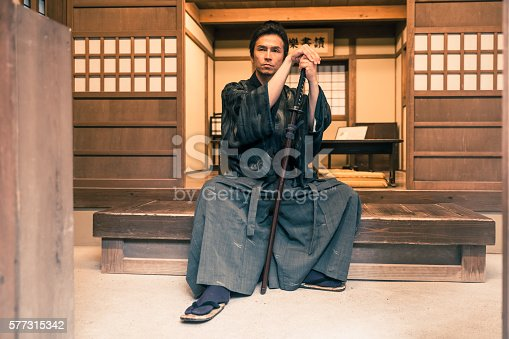Samurai sat on a wooden bench meditating with his katana