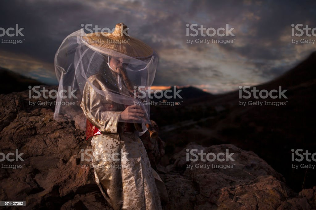 Samurai Woman in Golden colored Kimono and large straw hat playing japanese flute at dramatic sunset stock photo
