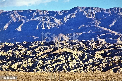 San Andreas Geologic Fault Line at sunrise in Coachella Valley near Palm Springs California USA.  In background the Little San Bernardino Mountains in Joshua Tree National Park.  Unusual abstract images in the erosion of rock and dirt rising at geologic fault epicenter.  Impressive example of tectonic forces.