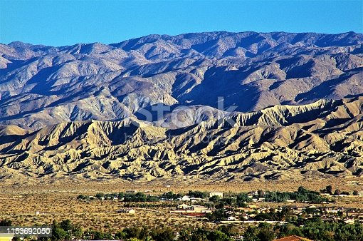 The San Andreas Geological Fault Line at sunrise in Coachella Valley near Palm Springs California USA.  With Little San Bernardino Mountains in Joshua Tree National Park in background.  Homes basically built right next to the fault zone epicenter.