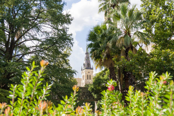 San Antonio River Walk with Church Tower Steeple Behind Trees stock photo