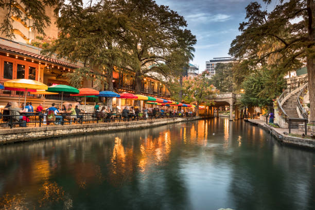San Antonio Riverwalk canal San Antonio: The San Antonio River Walk is a network of walkways along the banks of the San Antonio River, one story beneath the streets of San Antonio, Texas, USA. Lined by bars, shops, restaurants, nature, and public art, the River Walk is an important part of the city's urban fabric and a tourist attraction in its own right. san antonio texas stock pictures, royalty-free photos & images