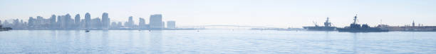San Diego bay panoramic on hazy day Scenic panoramic of San Diego bay including downtown, Coronado bay bridge and Coronado Naval Base on summer day naval base stock pictures, royalty-free photos & images
