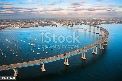 The unique curvature of the Coronado Bay Bridge spanning San Diego Harbor joining two cities; San Diego and Coronado.  I shot this image at dusk after a winter storm from a helicopter during a chartered photo flight at about 300 feet elevation.