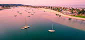 Pink sunrise Aerial drone view above marina harbor cove with calm waters and boats , sailboats , and yatchs along Sandy Beach along West Coast panoramic