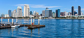 A panoramic sunny day view of San Diego Downtown Skyline by the San Diego Bay, looking from Coronado Peninsula, San Diego, California, USA.