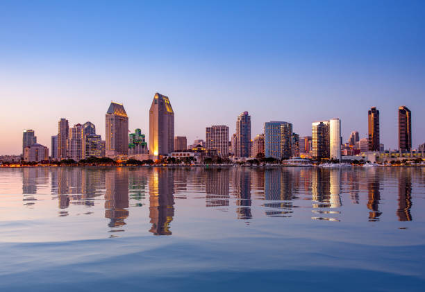 San Diego Skyline at sunset from Coronado Sunset illuminating the tall skyscrapers of San Diego in California from Centennial Park in Coronado with artificial water reflection promenade stock pictures, royalty-free photos & images