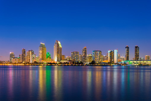 San Diego skyline (including the Grand Hyatt Hotel at left center) and San Diego Bay at dusk with building reflections.