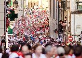 Pamplona, Spain - July 9, 2013: People run from bulls on street Santo Domingo during San Fermin festival in Pamplona