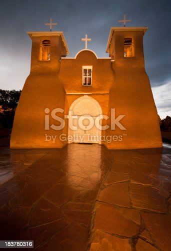 The San Francisco de Asis Mission is an old Spanish Mission located near Taos New Mexico.  The mission is illuminated on a rainy night.