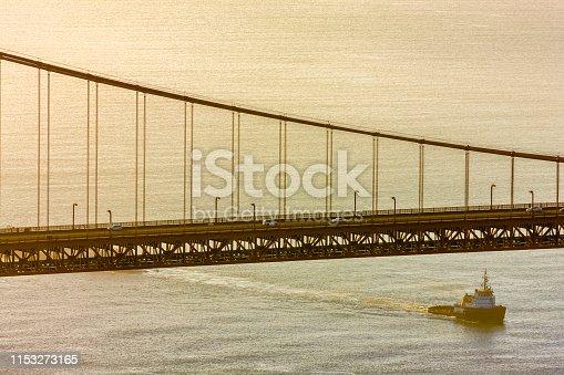 The Golden Gate Bridge and tugboat in San Francisco California at sunrise