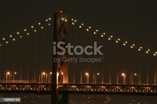 San Francisco Bay Bridge at Midnight mid week with no traffic.  Oakland Hills in the backhround.