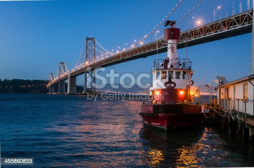 Shallow depth of field, twilight color photograph of the San Francisco Bay bridge from the embarcadero with a fireboat in the near foreground.