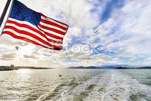 View of San Francisco Bay, the Golden Gate bridge, seagulls flying, the american flag waving and Alcatraz island at sunset from a ferry in California, United States.