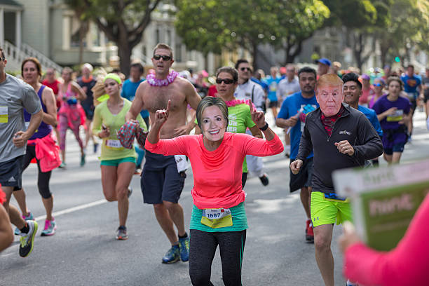 San Francisco Bay to Breakers 2016 Event San Francisco, CA, USA - May 15, 2016: This 12K race is one of the largest and oldest running events in the world. It attracts more than 50,000 runners and 100,000 spectators every year. This race includes both serious runners and those out for a fun Sunday run. Many wear fun and funky costumes to show their spirt. You will also find a few people in just their birthday suit. Two runner wearing Hillary Clinton's and Trump's masks. trump mask stock pictures, royalty-free photos & images