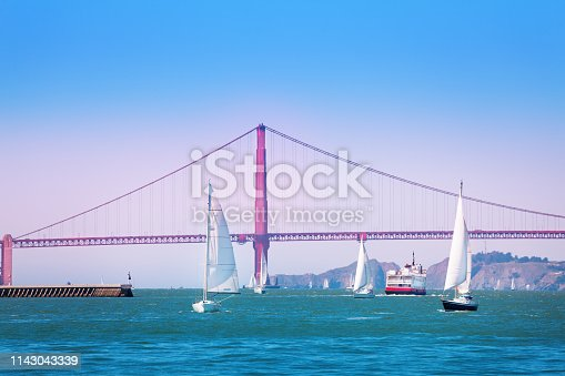 Beautiful seascape of San Francisco bay with yachts and ships passing under the Golden Gate Bridge, USA